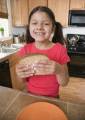 Hispanic girl eating sandwich in kitchen — Stok fotoğraf