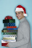 Young man holding holiday gifts — Stock Photo