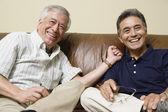 Retrato de homens idosos, sentado sobre o sofá rindo — Fotografia Stock