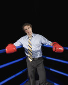 Businessman in corner of boxing ring with black eye — Stock Photo