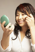 Asian woman applying makeup — Stock Photo