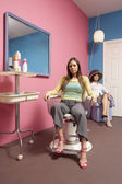 Young woman sitting in hairdresser's chair — Stock Photo