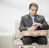 Indian businessman with briefcase looking at watch — Stock Photo