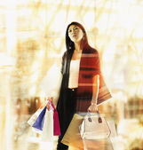 Jonge vrouw lopen boekwaarde shopping tassen — Stockfoto
