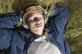 Teenage boy listening to headphones in grass — Stock Photo