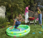 Young boy jumping into pool at barbecue — Stock Photo