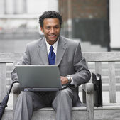 Indian businessman using laptop on outdoor bench — Stock Photo