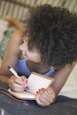 African American woman laying down and writing — Stock Photo