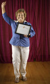 Woman holding certificate triumphantly — Stock Photo