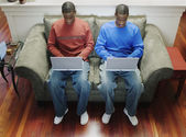 Kardeşler kanepede dizüstü bilgisayarlar ile — Stok fotoğraf