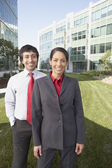 Hispanic businesswoman and businessman in front of office buildings — Stock Photo