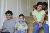 Portrait of four children sitting on stairs — Stock Photo
