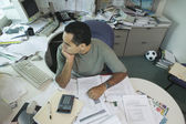 Businessman sitting at messy desk — Foto de Stock