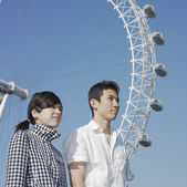 Young couple posing by Ferris wheel — Stock Photo
