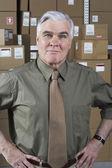 Businessman standing in warehouse — Stock Photo