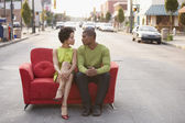 Young couple sitting on a couch outdoors — Stock Photo