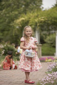 Young girl with Easter basket in garden — Stock Photo