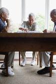 Three elderly men sitting at table playing game — Stock Photo
