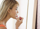 Hispanic woman applying lipstick — Stock Photo