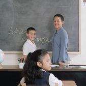 Enfants de l'école et enseignant en classe — Photo