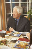 Senior Asian man eating at the dinner table — Stock Photo