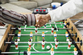 Shaking hands over foosball table — Stock Photo