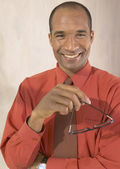 African man smiling and holding eyeglasses — Stock Photo