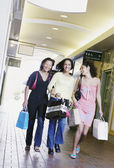 Three young women smiling walking together holding shopping bags — Stock Photo