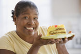 Middle-aged African woman smiling and holding up a piece of cake — Stock Photo