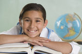 Hispanic girl leaning on textbooks and smiling — Stock Photo