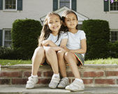 Portrait of two Indian sisters in front of house — Stock Photo