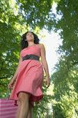 Vista dal basso della giovane donna nel parco con la borsa della spesa — Foto Stock