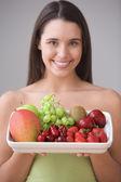 Portrait of teenage girl holding plate of fresh fruit — Stock Photo