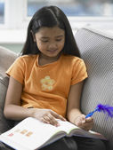 Young girl writing with a feather pen — Stock Photo
