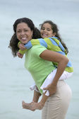 Portrait of mother giving daughter piggy back ride — Stock Photo