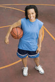 Portrait of teenage girl with basketball on court — Stock Photo