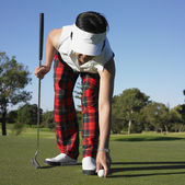 Asian woman placing ball on golf course — Stock Photo