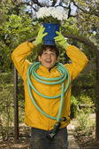 Boy holding potted plant on head and hose on shoulders — Stock Photo