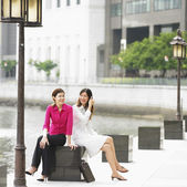 Two businesswomen sitting by water — Stock Photo