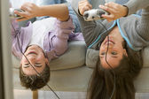 Two teenagers upside down on couch playing video games — Stock Photo