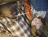 Two boys laying in hay — Stock Photo