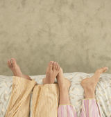 High angle view of couple's feet in bed — Stock Photo