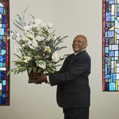 African man holding flower bouquet in church — Stock Photo