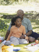 African grandfather and granddaughter at picnic — Stock Photo