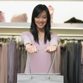 Young woman holding out a shopping bag — Stockfoto