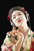 Asian woman in ethnic clothes listening to headphones — Stock Photo