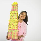 Hispanic girl carrying stack of gifts — Stock Photo