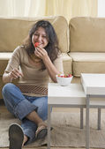 Young woman eating strawberries on living room floor — Stock Photo