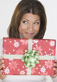 Portrait of woman holding gift and looking up — Stock Photo