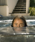 Portrait of Hispanic girl in swimming pool — Stock Photo